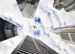 Plane flying above multiple tall buildings